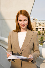 Businesswoman, with ginger hair, standing on balcony, holding document, smiling, front view, portrait
