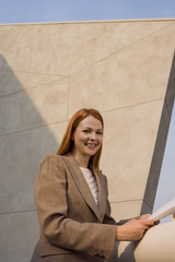 Businesswoman, with ginger hair, standing on balcony, holding document, smiling, side view, portrait