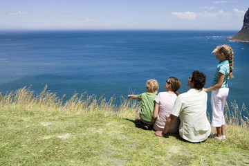 Family sitting on clifftop edge, looking at Atlantic Ocean horizon, rear view