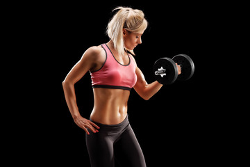 Attractive female bodybuilder lifting a barbell