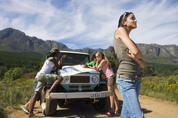 Four young adults leaning on jeep bonnet on dirt track in mountain valley, consulting map, bored woman waiting impatiently