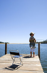 Girl (7-9) standing at edge of jetty, fishing in lake, rear view