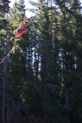 Teenage boy (12-14), in swimming shorts, swinging from rope above lake, side view, low angle view