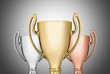 Close up golden,silver and bronze trophies on gray background
