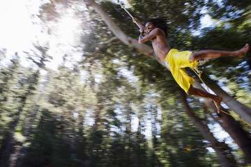 Boy (8-10), in yellow swimming shorts, swinging on rope above lake, low angle view (backlit)