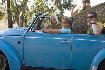 Four teenagers (17-19) sitting in blue convertible car with surfboard, portrait, side view