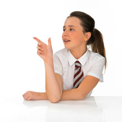 Young schoolgirl pointing to the left of the frame