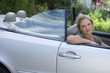Woman sitting in driving seat of parked convertible car on driveway, smiling, side view, portrait