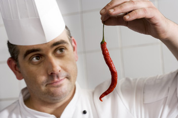 Male chef examining single red chilli pepper in commercial kitchen, close-up