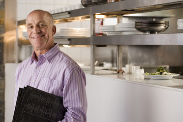 Male restaurant manager standing in commercial kitchen, carrying menus, smiling, side view, portrait