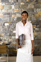 Waitress standing in restaurant, carrying menus, smiling, front view, portrait