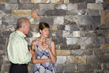 Mature man flirting with younger woman beside stone wall, holding glasses of white wine, woman looking away