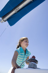 Girl (8-10) winding rope pulley of boat rigging on deck of sailing boat out at sea, smiling, low angle view