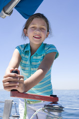 Girl (8-10) winding rope pulley of boat rigging on deck of sailing boat out at sea, smiling, front view, portrait