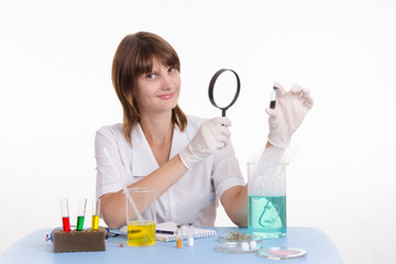 Pharmacist considers powder through a magnifying glass