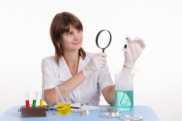 Scientist examines medicine through a magnifying glass