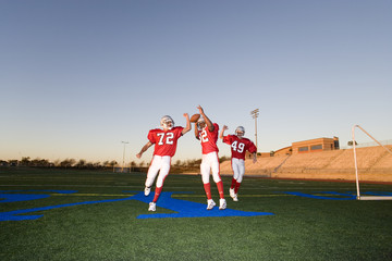 Three American football players, in red football strips, celebrating touchdown on pitch during competitive game at sunset