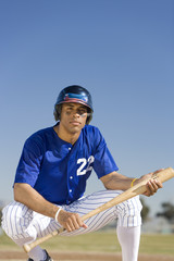 Baseball player wearing blue uniform and cap, crouching on pitch, holding bat, front view, portrait