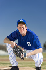 Baseball player wearing blue uniform, protective glove and cap, crouching on pitch, smiling, front view, portrait