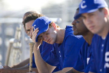 Dejected baseball team, in blue uniform, sitting on bench in stand during competitive baseball game, side view (differential focus)