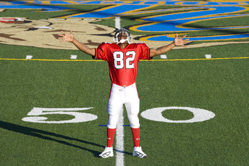 American football player, in red football strip and protective helmet, standing on pitch at 50 yard line, arms out, smiling, front view, portrait