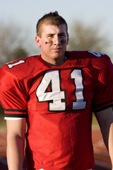 American football player wearing red football strip with number '41', standing on pitch, front view
