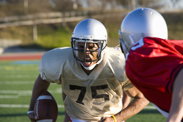 Determined American football player running with ball at opposing players during competitive game, snarling ferociously, front view
