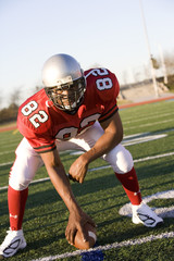 American football running back, in red football strip, crouching with ball in scrimmage line during competitive game, front view (tilt)