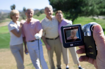 Man filming two mature couples standing on golf course, playing golf, focus on portable digital video recorder in foreground (tilt)