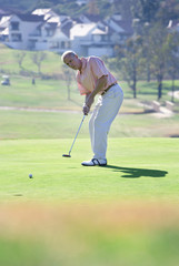 Mature man playing putting shot on green in mid-distance, focus on background