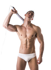 Sexy Man in White Brief Holding Massage Device