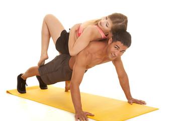 woman laying on man doing pushup looking