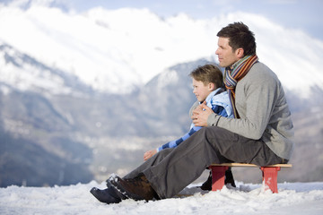 Father and son (7-9) sitting on sled in snow field, side view, mountain range in background