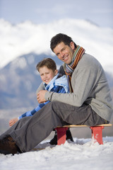 Father and son (7-9) sitting on sled in snow field, smiling, portrait, mountain range in background