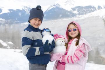 Boy and girl (7-9) wearing woolen hats in snow field, holding mini snowmen, smiling, portrait
