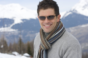 Young man wearing woolen scarf and sunglasses in snow, smiling, portrait, mountain range in background