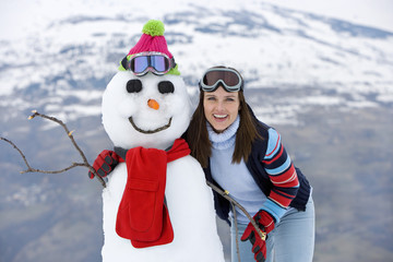 Young woman standing by snowman, smiling, portrait, mountain range in background
