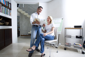Couple looking at paperwork in home office, smiling