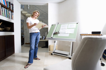 Woman standing by blue prints on drafting board in home office, smiling