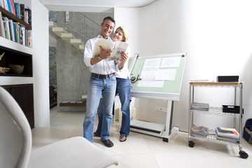 Couple standing in home office with paperwork, smiling