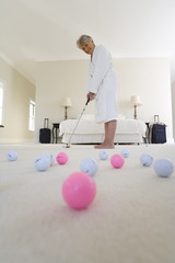 Senior woman standing in bedroom practising golf putt, smiling, portrait, golf balls in foreground