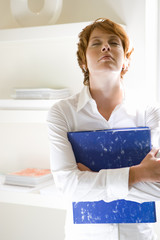 Businesswoman with folder, head back, eyes closed, close-up
