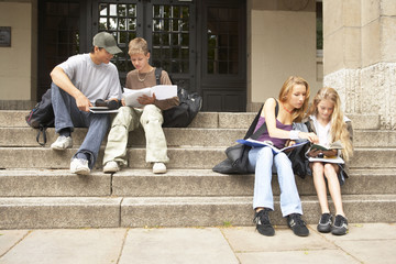 Young male and female students studying on the steps.