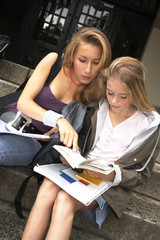 Two young female students studying on the steps.