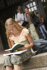 A young student studying on the steps.