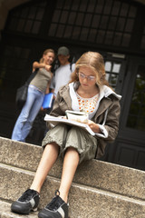 A young teenage student studying on the steps.