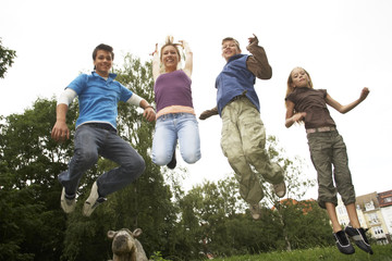 Teenage boys and girls jumping in a park.