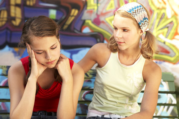 A dejected girl being consoled by another.