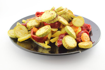 Fried vegetables on black plate