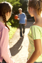 A boy holding a basketball walking towards two girls.